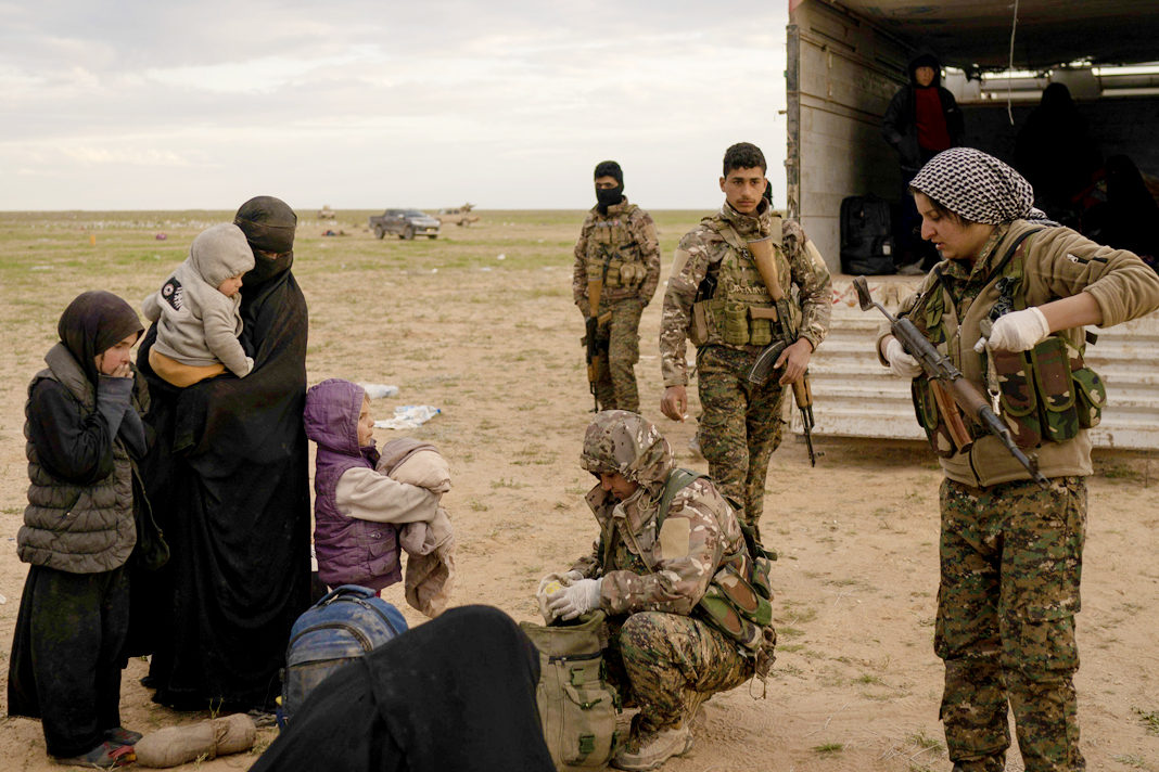 Women and children are screened by U.S.-backed Syrian Democratic Forces