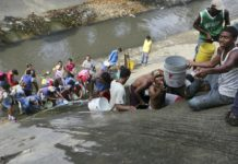 People collect water from an open pipe above the Guaire River. Fernando Llano, AP