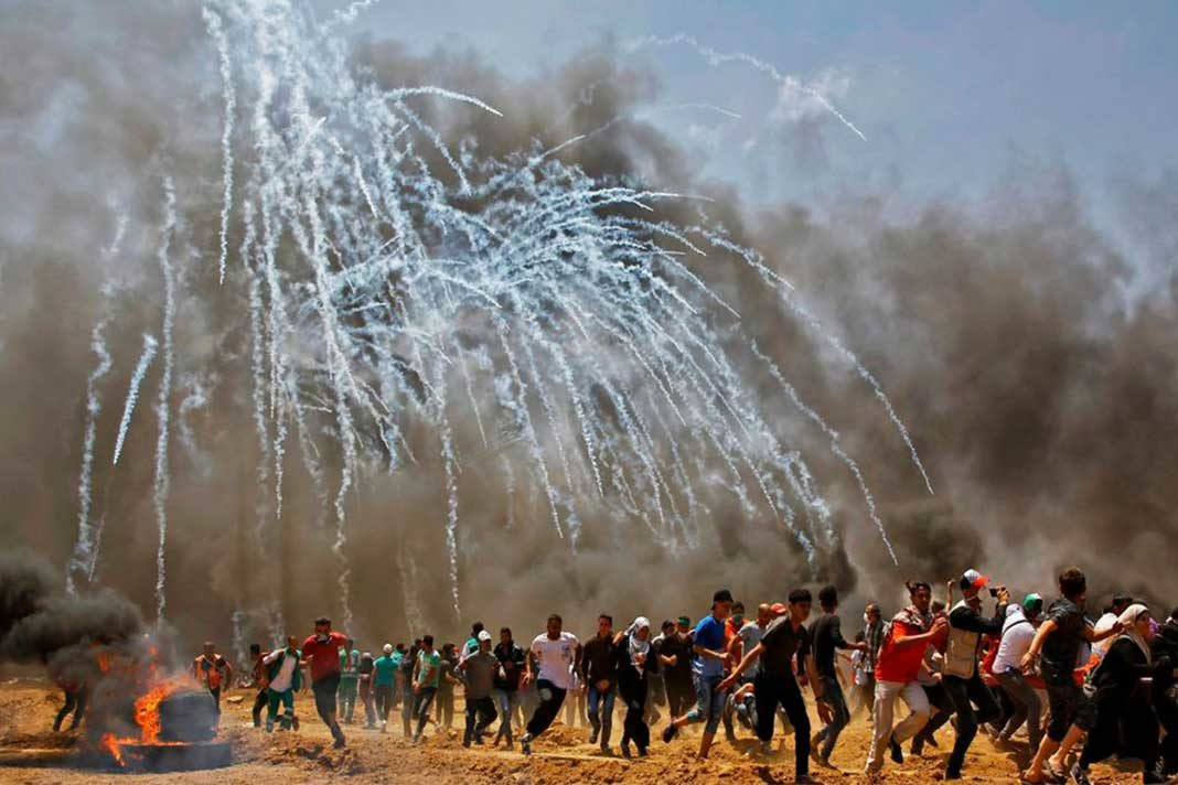Palestinians run for cover from tear gas during clashes with Israeli security forces near Gaza border