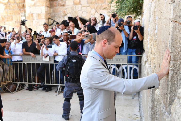Britains Prince William (L) talks to a guide on Jerusalem