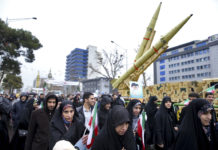 Iranians walk past a missile during a rally marking the 40th anniversary of the 1979 Islamic Revolution, in Tehran, Iran,