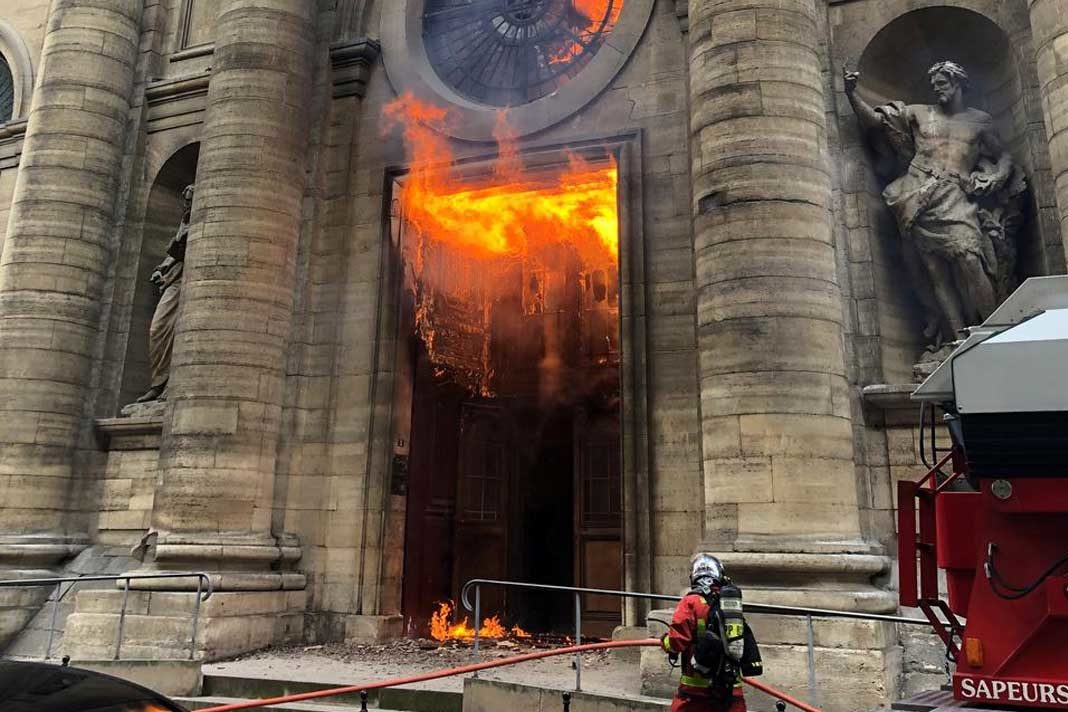 Members of the fire brigade run as a Saint-Sulpice church is seen on fire in Paris, France. (INSTAGRAM @agneswebste/via REUTERS)