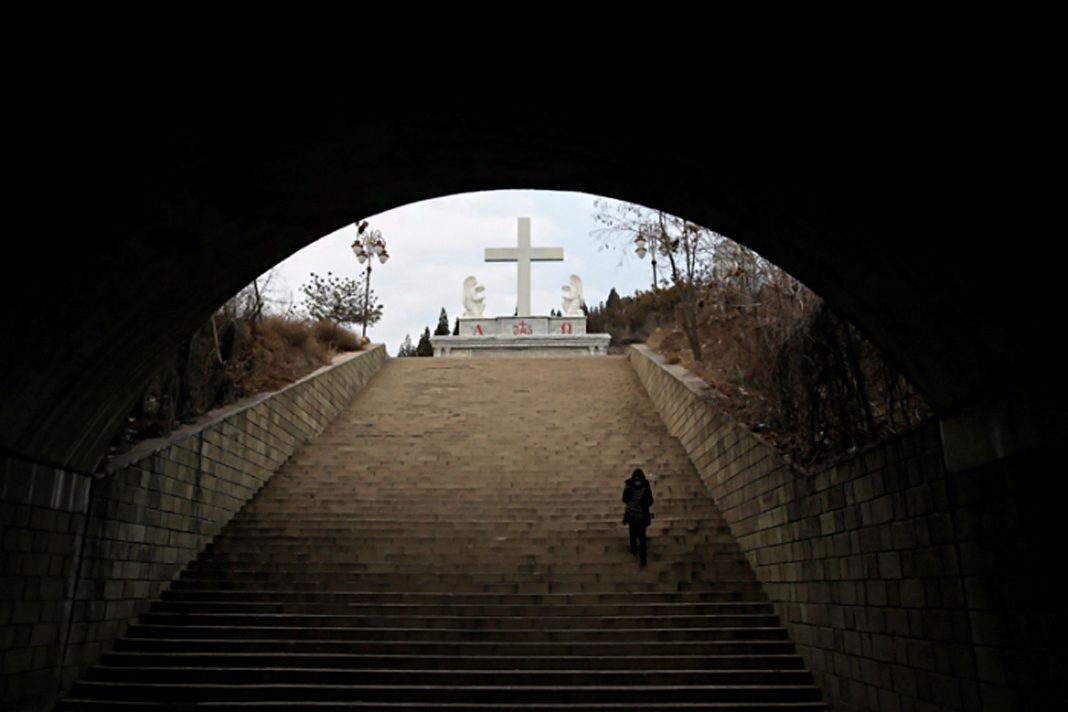 A villager climbs up the steps toward a cross near a Catholic church on the outskirts of Taiyuan, North China's Shanxi province, December 24, 2016. Picture taken on December 24, 2016. | REUTERS/Jason Lee