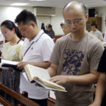 Ren Dejun, Liao Qiang, Peng Ran and Ren Ruiting follow a hymn book during service at a church in Taipei, Taiwan.