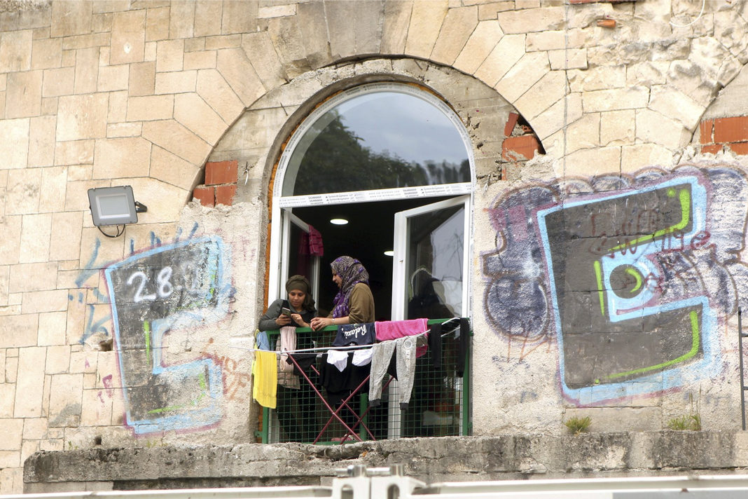 Two migrant women talk on the window of the abandoned building