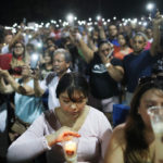People hold up their phones in lieu of candles at an interfaith vigil for victims of a mass shooting, which left at least 20 people dead, on August 4, 2019 in El Paso, Texas. A 21-year-old male suspect was taken into custody in the city which sits along the U.S.-Mexico border. At least 26 people were wounded. | Getty Images/Mario Tama