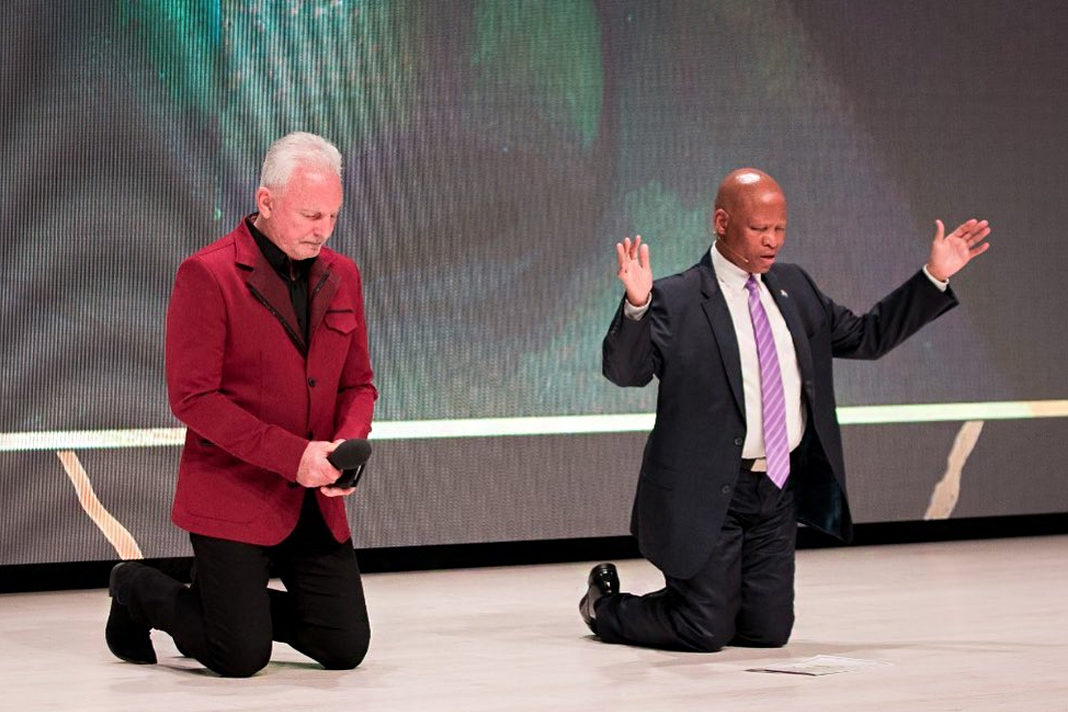 Rivers Church senior pastor André Olivier and Chief Justice Mogoeng Mogoeng share in a moment of prayer (PHOTO: Facebook).