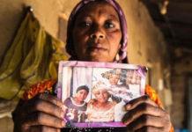 Leah Sharibu's Mother Rebecca Sharibu holds up her photo.