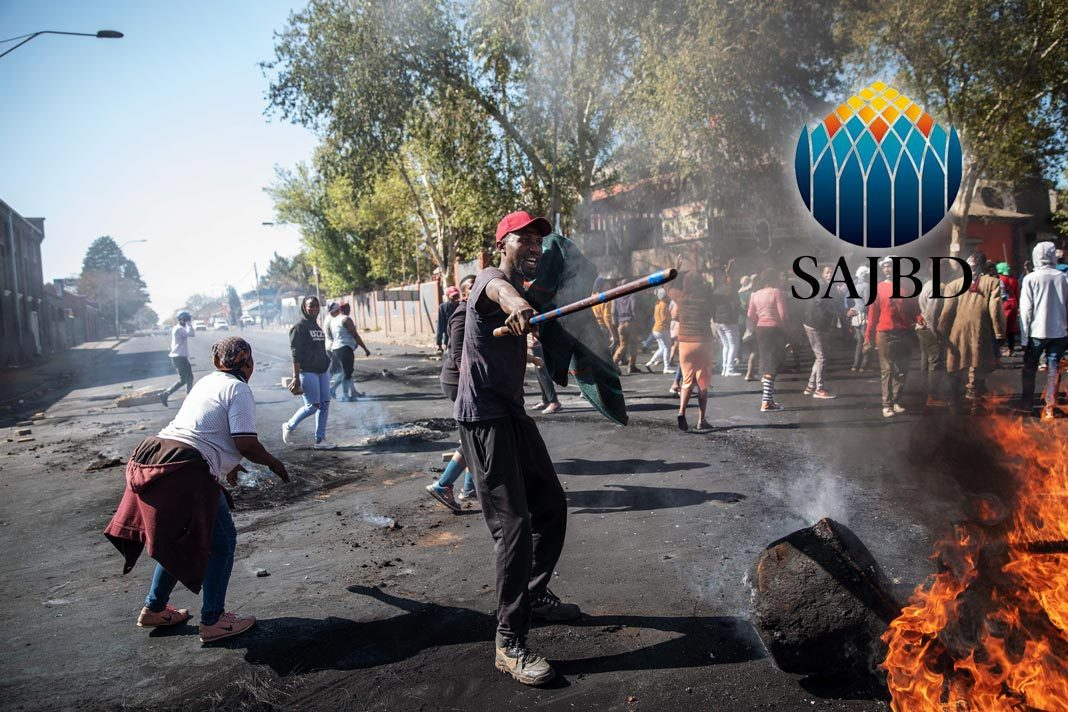 A man waves a stick in front a burning piece of furniture during a riot in the Johannesburg suburb of Turffontein on Sept. 2. Photographer: Michele Spatari/AFP via Getty Images