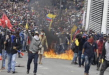 Enraged anti-government demonstrator gather during clashes with the police as they protest against President Lenin Moreno and his economic policies CREDIT: FERNANDO VERGARA/AP