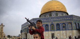 A Palestinian child plays with a toy gun on his father's shoulders at the Al Aqsa Mosque compound in Jerusalem's Old City
