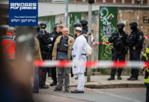 Jewish parishioners in traditional clothing and police forces stand near the scene of a shooting that left two people dead on Oct. 9, 2019, in Halle, Germany. (Jens Schlueter/Getty Images)