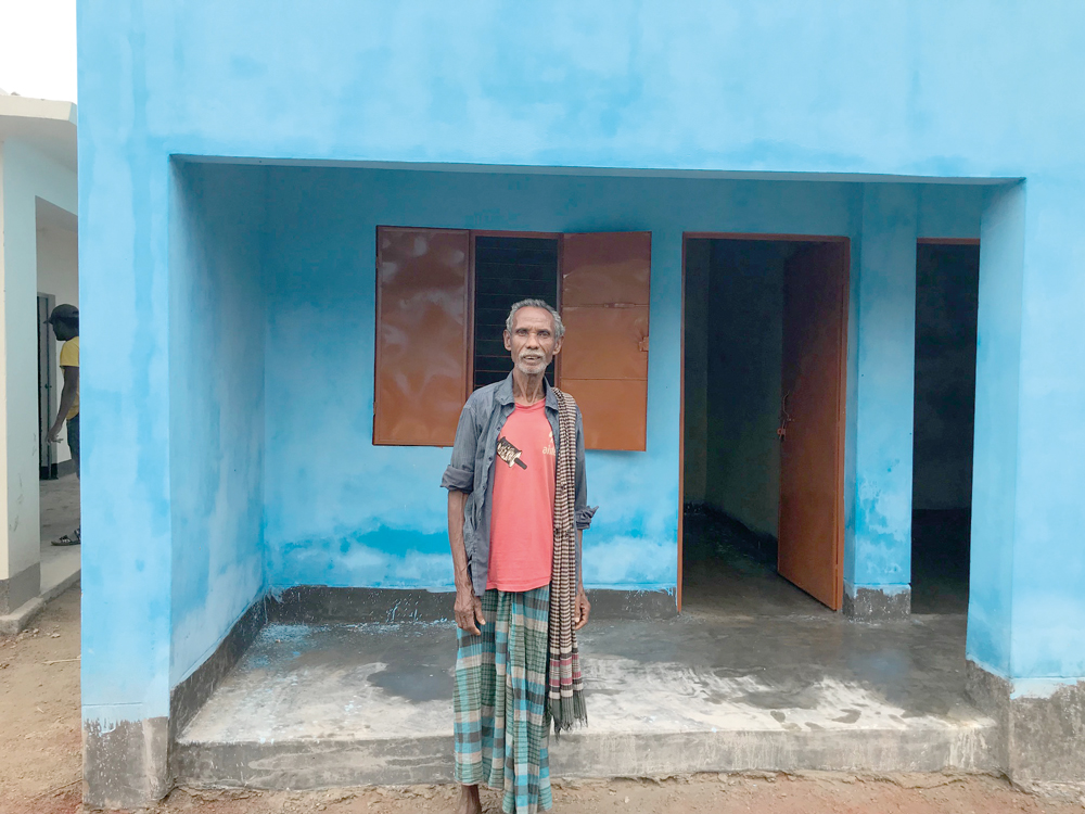 Dijen, standing outside his new house, sends his blessings to all those people he has never met who provided him and his family with a place to live