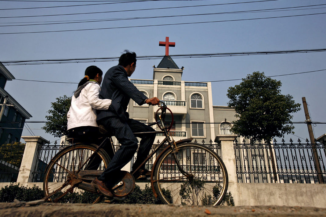 A local resident rides a bicycle past a church in Xiaoshan, a commercial suburb of Hangzhou, the capital of China's Zhejiang province, on Dec. 21, 2006 Lang Lang—Reuters