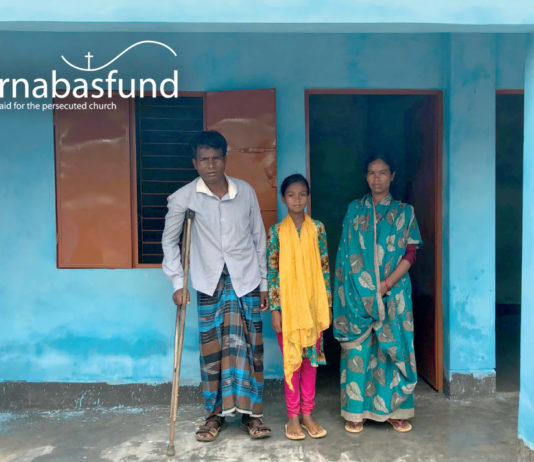Hopan Murmu (pictured with his family), who was shot in the leg as he fled an attack by authorities on his community, is thankful to God for his new Barnabas-built home