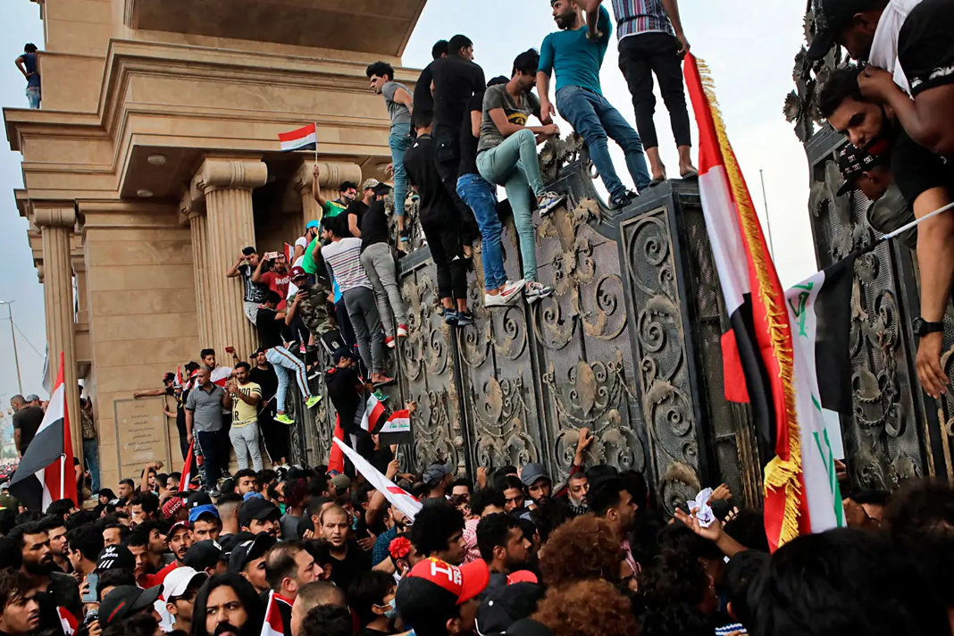 Anti-government protesters try to break into the provincial council building during a demonstration in Basra. AP