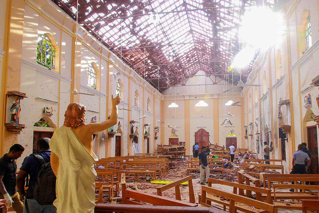 A blood-stained statue of Jesus Christ is pictured while officials inspect the site of a bomb blast, as the sun shines through the blown-out roof, inside St Sebastian's Church in Negombo, Sri Lanka, April 21, 2019. / Reuters Photo