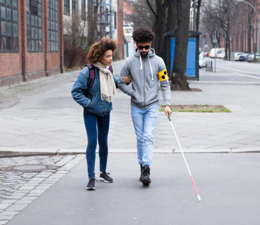 blind person walking with friend