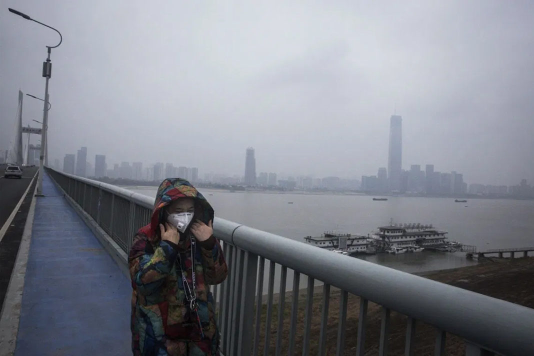 A woman wears a protective mask as she walks across the Yangtze River Bridge in Wuhan, China.