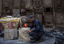 A federal police member lights a candle inside a church burned and destroyed by ISIS. CHRIS MCGRATH