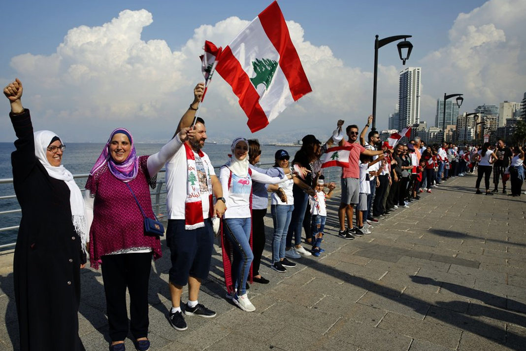 Anti-government protesters form a human chain as a symbol of unity, during ongoing protests against the Lebanese government, on the Mediterranean waterfront promenade, in Beirut, Lebanon. (AP Photo/Bilal Hussein)