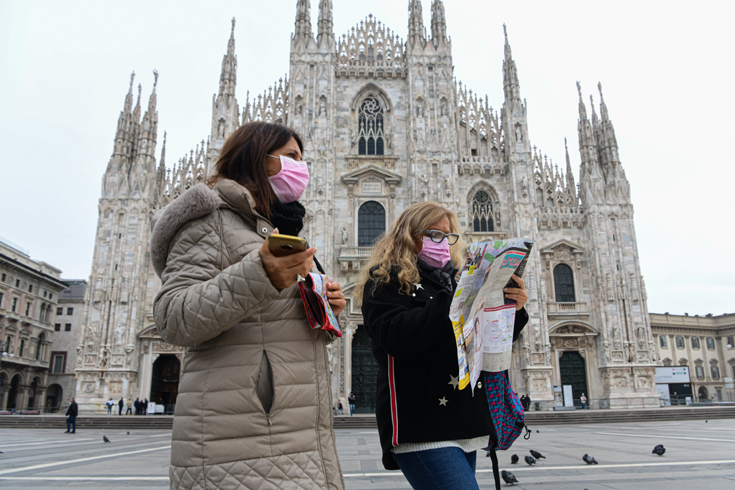 Two tourists from Argentina wear face masks walk in Piazza Duomo, Milan. /Piero Cruciatti /AFP