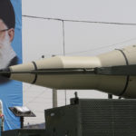 A Sajjil missile is displayed by Iran's Revolutionary Guard, in front of a portrait of Iranian supreme leader Ayatollah Ali Khamenei, during a military parade, Sept. 21, 2012. (AP/Vahid Salemi)
