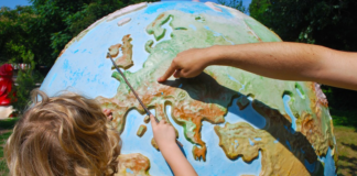 Child pointing to Europe on map