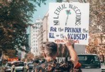 an activist holds a sign from Rehumanize International