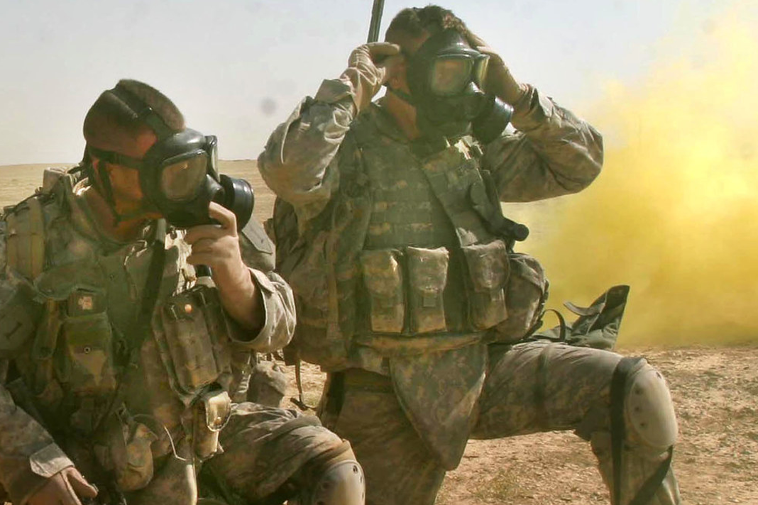 U.S. Army Soldiers put their gas masks on for a simulated chemical attack during a training mission near Camp Ramadi, Iraq, Sept. 25, 2007.