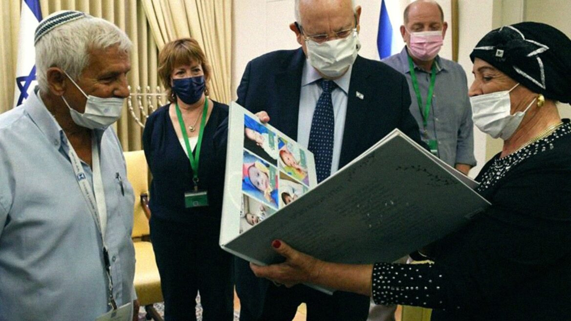 Angel Alon and husband Shlomo showing former President Reuven Rivlin one of the albums she made for a foster child. (Summit Institute)