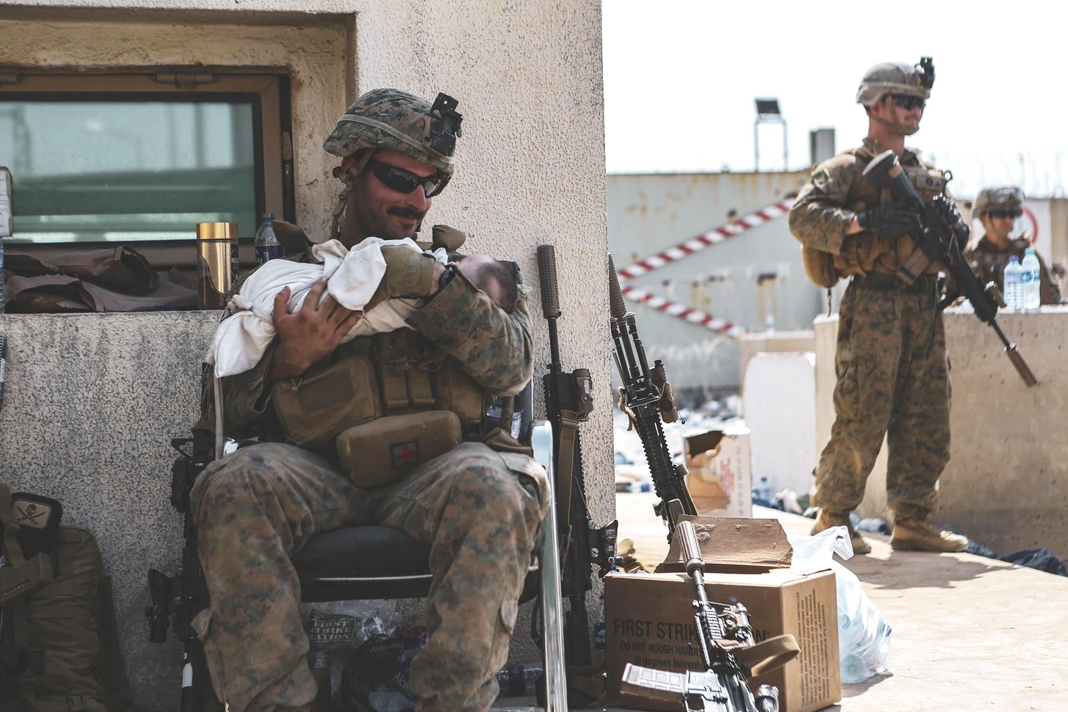 A Marine assigned to the 24th MEU calms an infant during an evacuation at #HKIA Kabul, Aug 20.